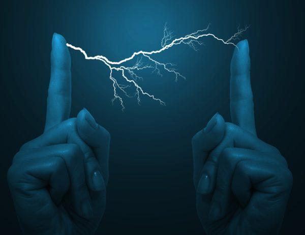 An electrical bolt between a woman's fingers