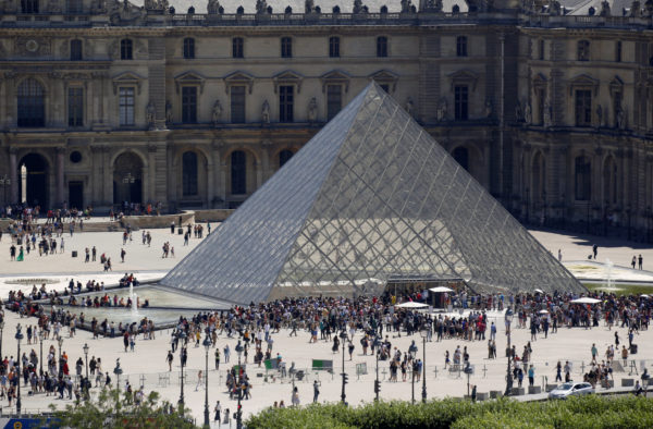 A view shows tourists walking past the Louvre Pyramid designed by Chinese-born U.S. architect Ieoh Ming Pei outside the Louvre Museum in Paris, France, on July 4, 2019. Photo by Regis Duvignau/Reuters
