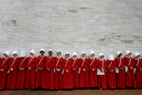 """Women dressed as handmaids promoting the Hulu original series """"The Handmaid's Tale"""" stand along a public street during the 2017 South by Southwest (SXSW) Music Film Interactive Festival 2017 in Austin, Texas. Photo by Brian Snyder/Reuters"""