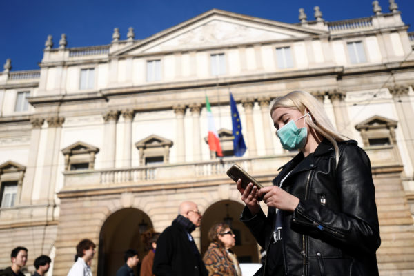 A woman wearing a face mask checks her phone outside the Teatro alla Scala, closed by authorities due to a coronavirus outbreak, in Milan, Italy February 24, 2020. Photo by Flavio Lo Scalzo/Reuters