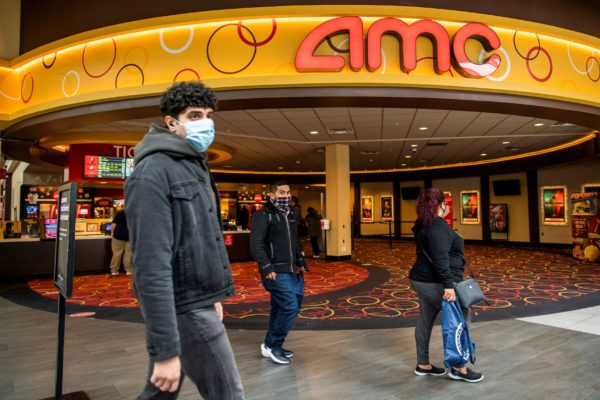 FILE PHOTO: People wear face masks as they walk by a movie theater during the coronavirus disease (COVID-19) pandemic in N...