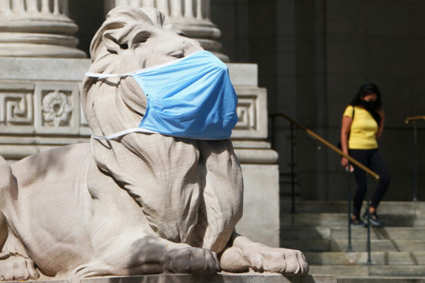 A lion statue that sits outside the New York Public Library building wears a mask